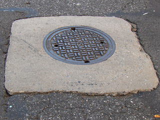Uneven gradient transition from road to concrete manhole collar